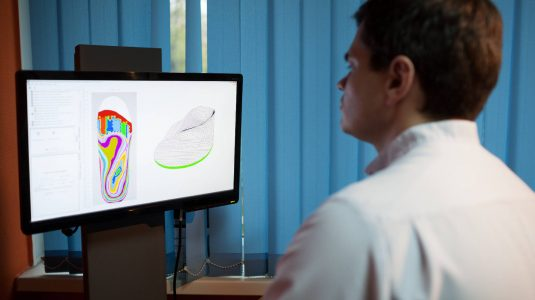 Orthopaedist at work with computer. He modeling orthopedic shoe using foot scan