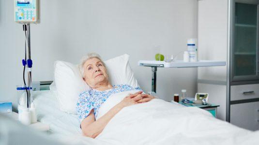 Senior female lying in bed in hospital ward